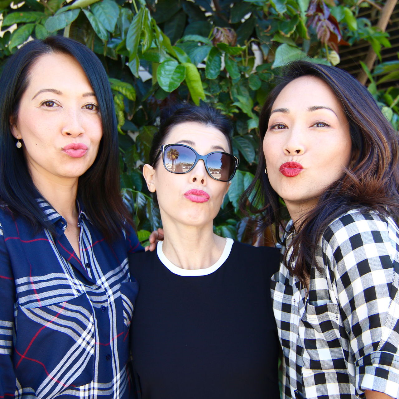 Three women blowing kisses showing their lipstick color